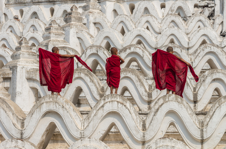 buddhist structures: Back side of three young monk change the robe on the Mya Thein Tan Pagoda at bagan, mandalay, myanmar