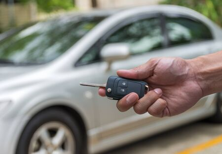 used car: Hand holding the keys over photo blurred of used car for open the door car, transportation and ownership concept Stock Photo