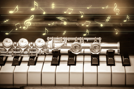 flute structure: Closeup Flute on the keyboard of piano with music demody, musical instrument, vintage tone
