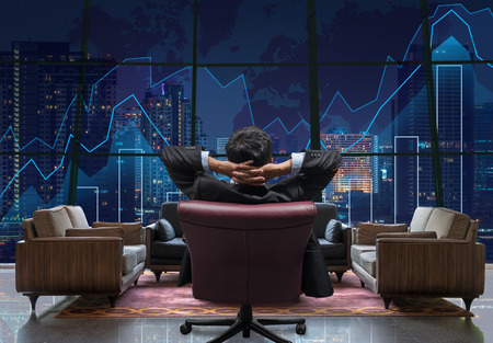 investment strategy: Back side of sitting businessman who is looking at Trading graph on the cityscape at night background,lobby sofa from dicut and retouch each elements, Business financial and investment concept Stock Photo