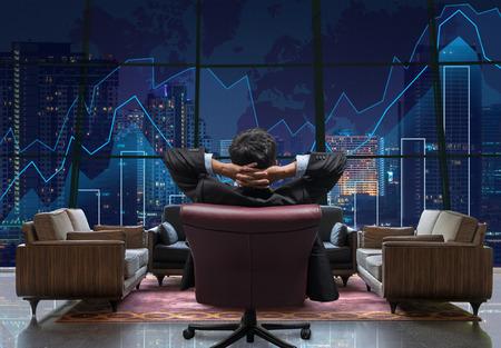 El lado trasero de sentarse empresario que está mirando el gráfico de comercio en el paisaje urbano en el fondo de la noche, el sofá del vestíbulo de dicut y retocar cada elemento, de negocios y el concepto de inversión financiera