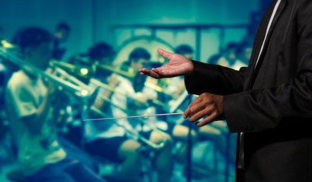a rehearsal: Orchestra conductor hands leading over the Abstract blurred photo of classic music band when rehearsal, musical concept