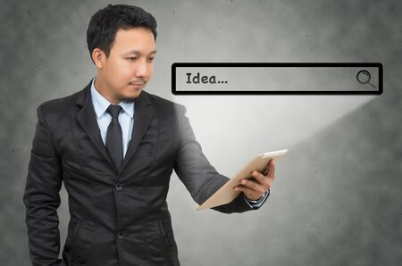 url virtual: Asian businessman using the tablet with browsing of Internet searching �Idea� bar on the wall background, Internet concept Stock Photo