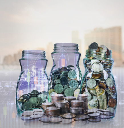 global investing: Double exposure of stack of coins and mix coins in clear bottle on blurred photo of cityscape and financial graph with cityscape background, Business Trading and investing concept Stock Photo