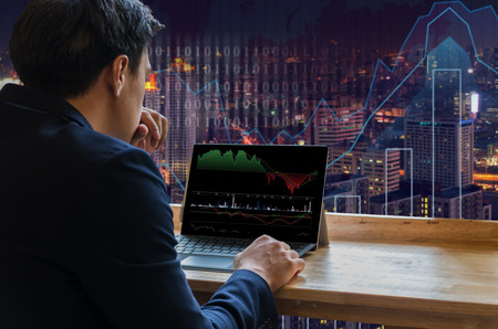 conqueror: Businessman sitting and using computer laptop showing trading graph beside the windows glass over the Trading graph on the cityscape background, Business financial concept Stock Photo