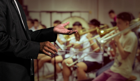 Orchestra conductor hands leading over the Abstract blurred photo of classic music band when rehearsal, musical concept
