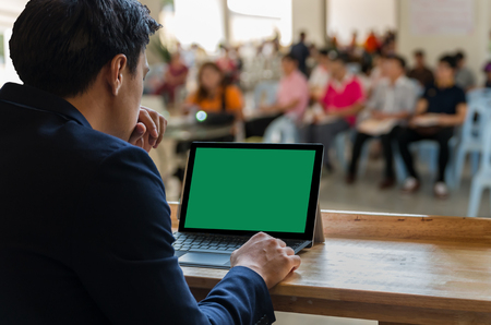 hall monitors: Businessman sitting and using computer laptop showing the blank green screen over the Meeting Blurred background at bright conference hall, Business meeting concept