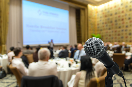attendee: Microphone over the Abstract blurred photo of conference hall or seminar room with attendee background