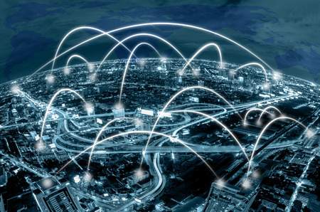 Network connection line between building over the top view of cityscape background and world map background which dicut each elements, cool tone color,business social network and connection concept