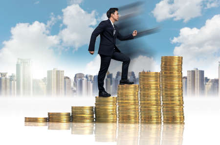 Businessman goes up the stack of gold coins on a photo blurred cityscape, business investment and success concept