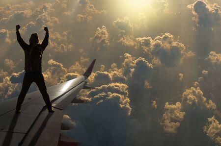 show hands: silueta del hombre que muestran las manos sobre el sol con las nubes en ala de avión, concepto de negocio Challenge