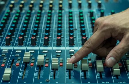 Closeup Hand adjusting audio mixer, music instrument concept Stock Photo