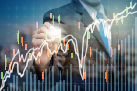 Businessman writing the trading graph of stock market on the virtual screen on dark background, Business stock market concept