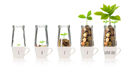 Gold coins and seed in five clear bottle over the glass with text good idea on white background,Business investment growth concept Stock Photo