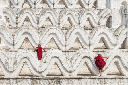 clambering: Two young monk are Clambering on the Mya Thein Tan Pagoda at bagan, mandalay, myanmar