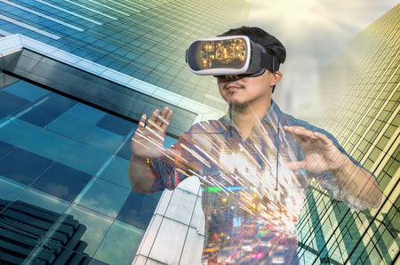 Double exposure of Asian man wearing virtual reality over the Modern business building glass of skyscrapers background, VR with business building concept 스톡 콘텐츠