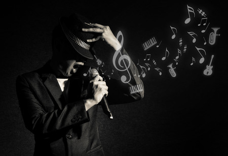 Songer hand holding the microphone and singing with music notes or melody on black background, musical concept