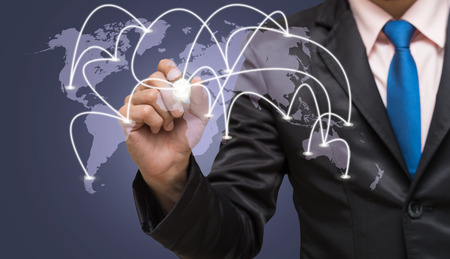 business globe: Businessman writing the center point of connection line of global network on world map with dark blue background, business connection concept Stock Photo