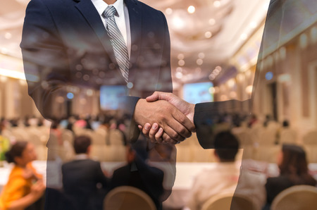 attendee: Double exposure of businessman handshake over the Abstract blurred photo of conference hall or seminar room with attendee background, business agreement concept
