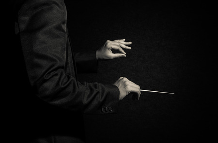 conducting: Orchestra conductor hands, Musician director holding stick on dark background