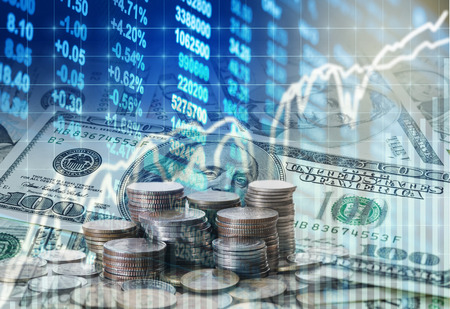 Stack of coins and american dollars money over the LED display Stock market exchange data background, Business investment and trading concept Foto de archivo