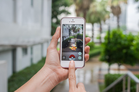 iphone5: Bangkok, Thailand - Aug 7, 2016 : Hand holding Apple iphone5 mobile phone showing the Pokemon Go application at screen over the walk way with park photo blurred background on August 7, 2016, thailand