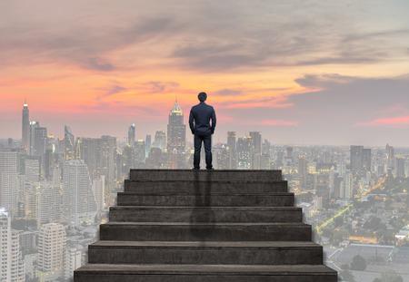Empresario de pie para subir escaleras sobre el paisaje urbano bajo el cielo en el crepúsculo tiempo fondo, negocios y ambiciones Concepto del éxito Foto de archivo