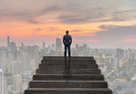 Businessman standing for walking up stairs over the cityscape under the sky at twilight time background,Success business and Ambitions concept Standard-Bild