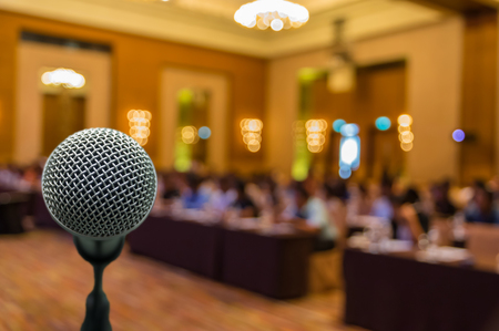 convention center: Microphone over the Abstract blurred photo of conference hall or seminar room with attendee background