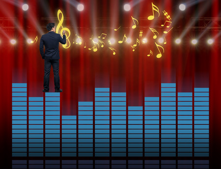 Businessman standing over the sound waves equalizer and drawing the music note on red curtain background,musical concept Stock Photo