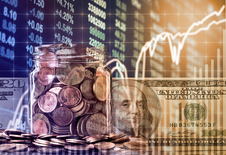 Gold coins in clear bottle and american dollars money over the LED display Stock market exchange data background, Business investment and trading concept Stock Photo