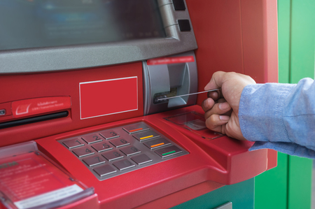 automatic transaction machine: Closeup of male hands using and with insert ATM card into bank machine for withdraw the money, business technology banking concept Foto de archivo