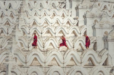 Three young monk are running and jumping on the Mya Thein Tan Pagoda at bagan, mandalay, myanmar