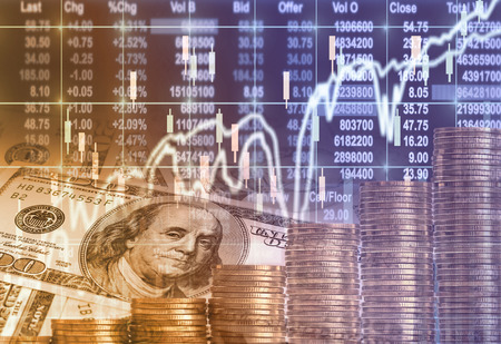Stack of gold coins and american dollars money over the LED display Stock market exchange data background, Business investment and trading concept