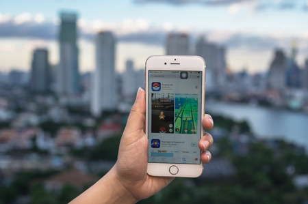 iphone5: Bangkok, Thailand - Aug 7, 2016 : Hand holding Apple iPhone5 mobile phone showing the Pokemon Go application at screen over the bangkok cityscape photo blurred background on August 7, 2016, thailand