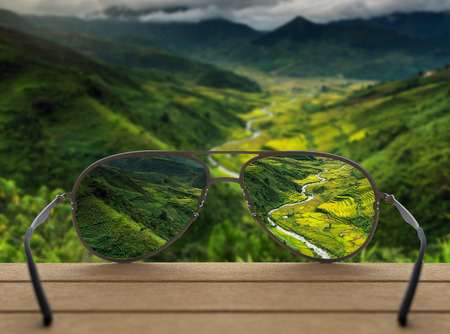 Conceptual image of Landscape focused in glasses lenses over the photo blurred of Top view point which can see Rice terraced fields background Stock Photo