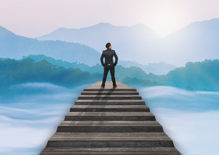 Businessman climbed on top of the stairs over the cityscape which can see beautiful scenary of mist with mountain range, Success business and Ambitions concept