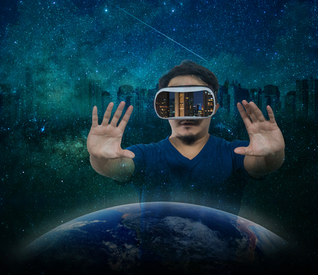 double game: Double exposure of Asian man wearing virtual reality showing the building cityscape over milky way and star with the earth and cityscape background Stock Photo