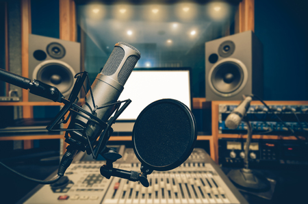 Professional condenser studio microphone over the abstract photo blurred of music studio background, Musical instrument Concept