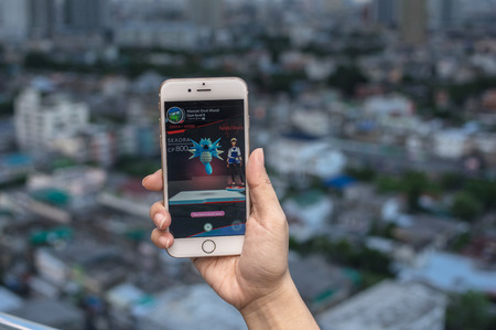 Bangkok, Thailand - Aug 7, 2016 : Hand holding Apple iPhone5 mobile phone showing the Pokemon Go application at screen over the bangkok cityscape photo blurred background on August 7, 2016, thailand