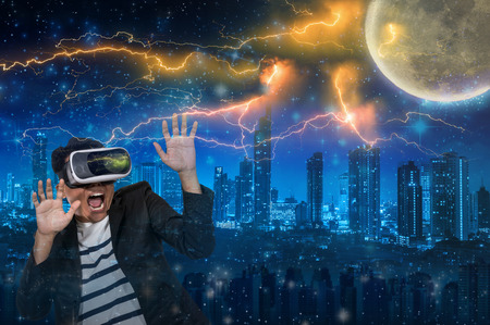 Double exposure of Asian man wearing virtual reality in scared action Looking the thunder lightnings over star and moon with the cityscape background, VR concept Stock Photo