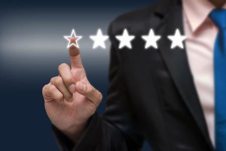 暗いトーンの背景、ビジネス評価概念にホテルや会社の評価を高める、評価を高める 5 つの星のシンボルを指してビジネスマン