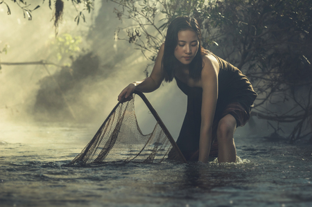 folkways: A beautiful Village women fishing sunrise at the nature river, countryside and Folkways concept