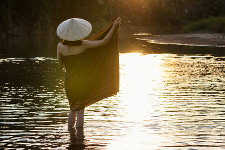 Backside of A beautiful Village women undress at the nature river when sunrise with lens flare, countryside and Folkways concept Stock Photo