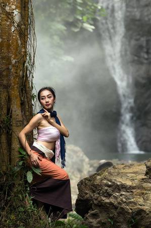A beautiful Village women standing over the waterfall background, countryside and Folkways concept