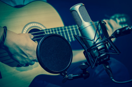 Professional condenser studio microphone over the abstract photo blurred of Closeup musician play the guitar, Musical instrument Concept