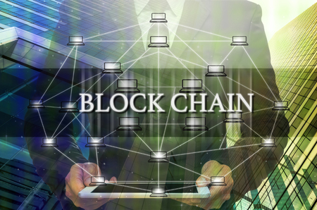 building a chain: Block chain Text and Distributed computer network with Businessman holding the tablet over the Modern business building glass of skyscrapers, Distributed ledger technology and block chain concept