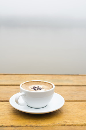 White coffee cup on wood table beside the river view over the fog background