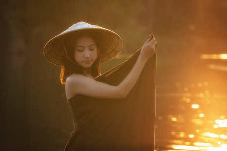 folkways: beautiful Village women undress at the nature river when sunrise with lens flare, countryside and Folkways concept Stock Photo