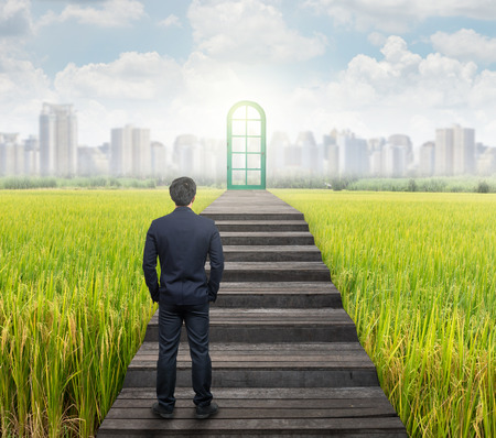 Businessman standing for walking up stairs to the door over the  grass and cityscape background,Success business and Ambitions concept Stock Photo